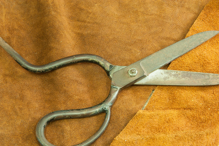 Scissors for cutting leather on  wooden  Stock Photo