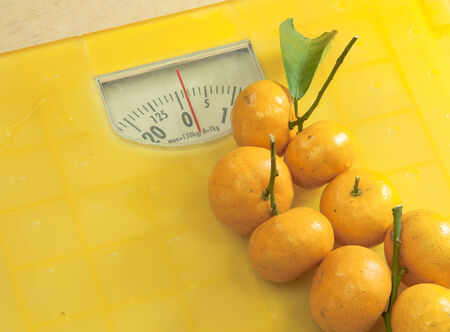 Weighting scales yellow with tangerines put on top Stock Photo