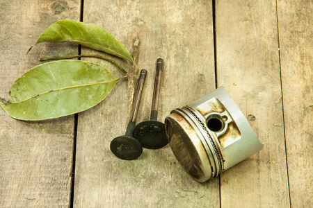 Old piston and dry leaf laying on the wooden floor. photo