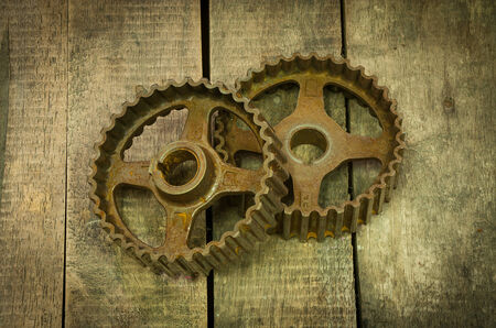 Pinion gears meshing together on wooden background. Stock Photo