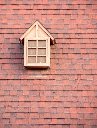 pane: Window shaped like a house on a brick wall.