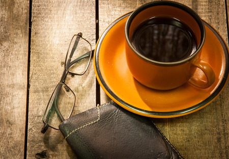 wallet, glasses, pen and cup of coffee in wood table