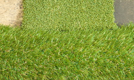 Artificial grass placed on the wooden floor. Stock Photo