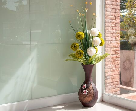 Vase of flowers is placed near the window.
