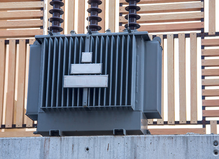 Electricity distribution transformer with cooling ribs on wood wall
