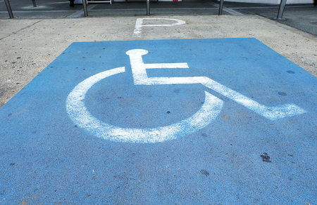 handicapped parking spot. logos for disabled on parking. disability symbol painted on the floor.