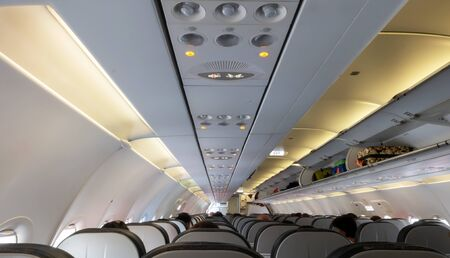 passengers traveling by a plane. Travel concept. Roofs and seats inside the plane. Фото со стока
