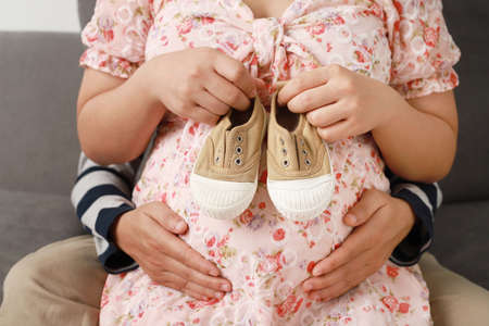 A pregnant woman holds a baby's foot singing, while her husband took the handle of her big belly, concept family photo.