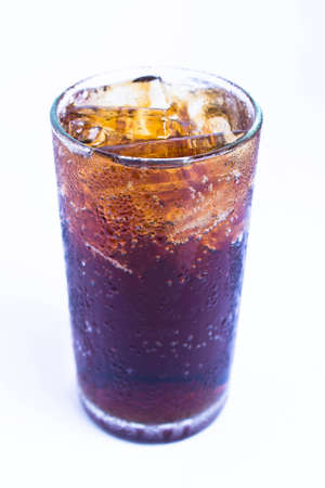 Photo of fizzy Cola in a glass with ice, isolated on a white background