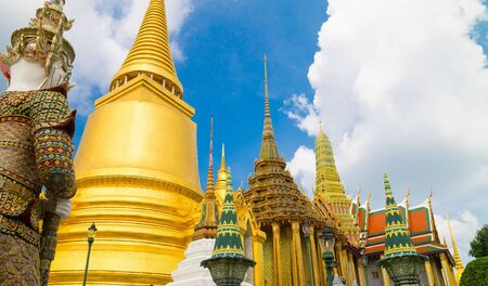 east asia: Grand Palace and Wat Phra Kaew Temple interior, Bangkok, Thailand  The Emerald Buddha temple  Visible are one of the many Buddha temple in interior of Grand Palace  Dramatic cloudscape with blue sky and cumulus clouds over the Grand Palace  Specific Thai