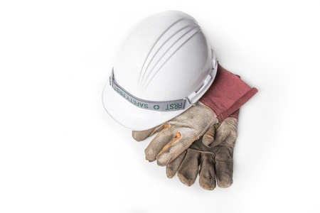 Plastic safety helmet and Dirty old leather gloves on white background