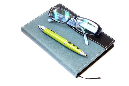 Glasses and pen on the notebook, close up photo