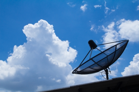 the satelite dish of cable tv for home use on the roof of building photo