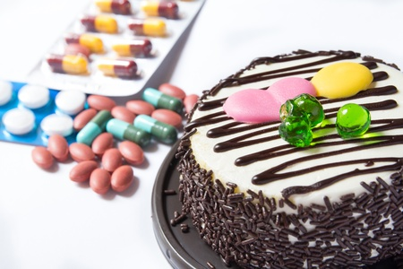 chocolate cake and many medicine on white background photo
