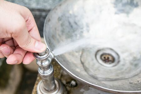 Mans hand turns on the drinking water faucet at public park. photo