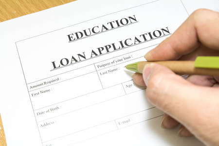 education loan: Man filling out a education loan application Stock Photo