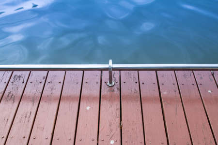 guard rail: backgrounds of wood floor with guard rail and green water