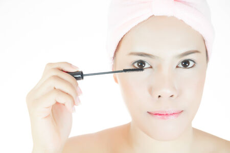 Beautiful asian young adult woman face with mascara brush photo