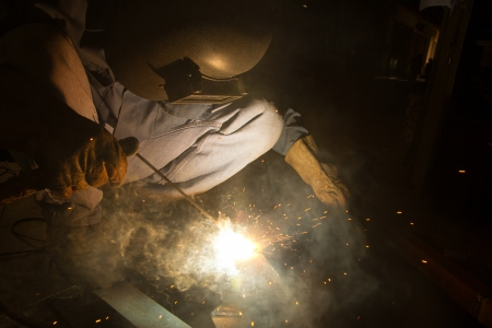 Welder with sparks arcing, industrial background photo