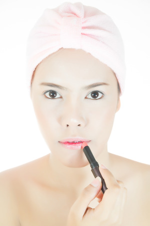 Beautiful asian young adult woman puts on lipstick and pouts her lipsr photo