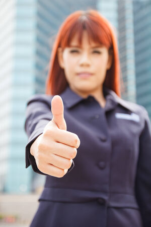 portrait of the smiling asian business woman that shows the thumbs up at modern building photo