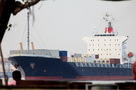 Large container ship in river, industrial background.