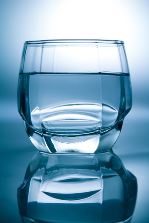 Glass filled with water isolated with reflection photo