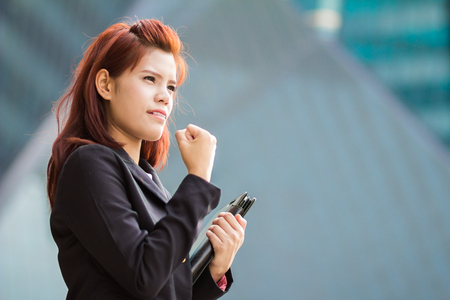 asian success Businesswoman holding document file at outdoor office. photo