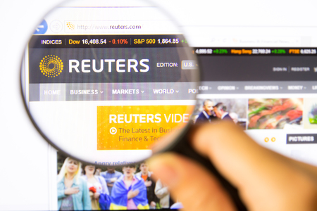 Bangkok,Thailand – APRIL 20, 2014: Photo of Reuters Monitor homepage on a monitor screen through a magnifying glass.