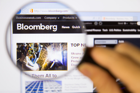 Bangkok,Thailand – APRIL 20, 2014: Photo of bloomberg Monitor homepage on a monitor screen through a magnifying glass.