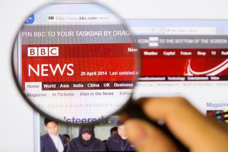 Bangkok,Thailand – APRIL 20, 2014: Photo of BBC Monitor homepage on a monitor screen through a magnifying glass.