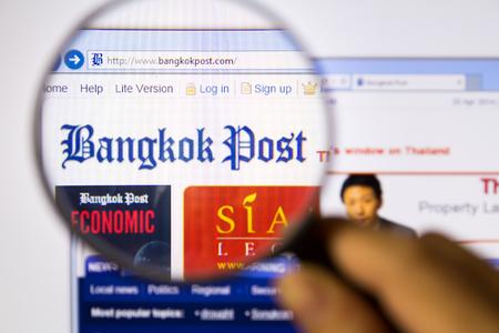 Bangkok,Thailand – APRIL 20, 2014: Photo of Bangkok Post Monitor homepage on a monitor screen through a magnifying glass.
