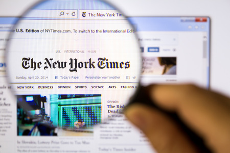 new york times: Bangkok,Thailand – APRIL 20, 2014: Photo of The New York Times Monitor homepage on a monitor screen through a magnifying glass.