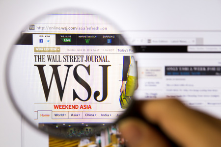 Bangkok,Thailand – APRIL 20, 2014: Photo of The Wall Street Journal Monitor homepage on a monitor screen through a magnifying glass.