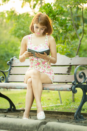 Beautiful Asian young woman reading in the park photo