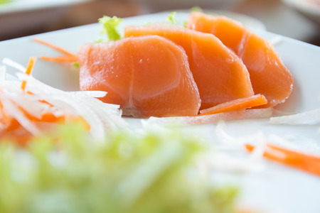 Salmon sashimi on white dish, food background photo