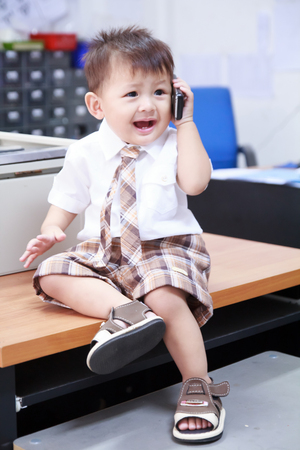 The little boy in business suite talking phone. photo