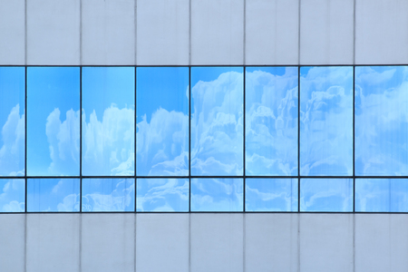 Clouds reflected in windows of modern office building Editorial