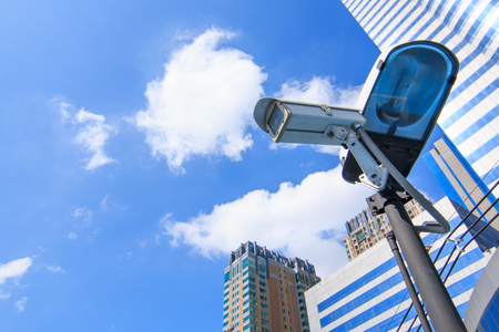 Camera system guarding blue skyscraper office building with sky above photo