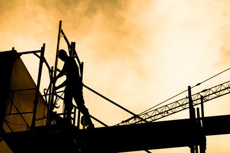 travailleur: Silhouette de travailleurs de la construction sur l'�chafaudage de travail sous un soleil chaud Banque d'images