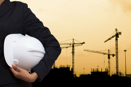 engineer holding white helmet for workers security on background of building construction