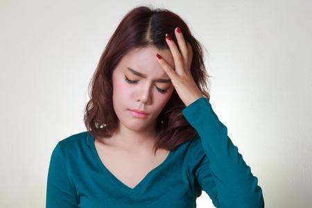 Headache. Young asian woman having a headache 스톡 콘텐츠