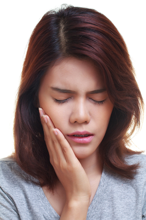tooth ache: Teen woman pressing her bruised cheek with a painful expression as if shes having a terrible tooth ache. Stock Photo
