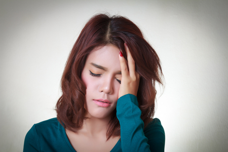 Headache. Young asian woman having a headache Imagens
