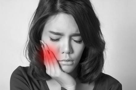 Mujer adolescente presionando su mejilla amoratada con una expresión de dolor, como si ella está teniendo un dolor terrible del diente.