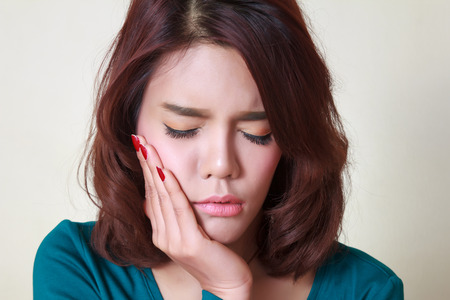 Teen woman pressing her bruised cheek with a painful expression as if shes having a terrible tooth ache. Stock Photo
