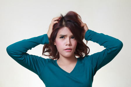 desperately: Stress. Woman stressed is going crazy pulling her hair in frustration. Stock Photo