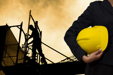 engineer holding Yellow helmet for workers security on background of building construction 스톡 콘텐츠