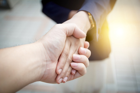 saludo de manos: Las mujeres de negocios apret�n de manos en el fondo brillante