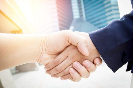 saludo de manos: Las mujeres de negocios apretón de manos en el fondo brillante